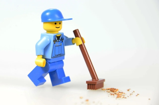 Lego mini figure with a broom sweeping up sawdust